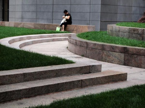 Woman with dog on Federal Plaza garden