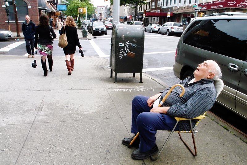 Asleep on a sidewalk along Graham Avenue