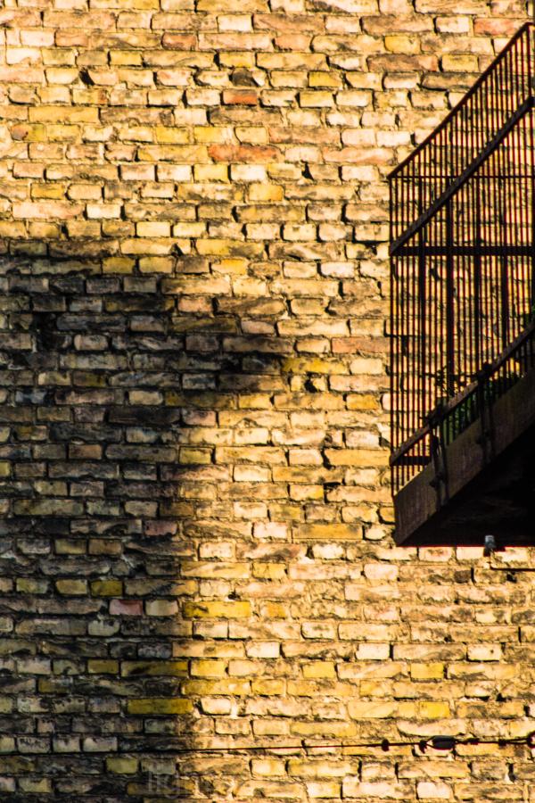 Shadowed brick wall with railings