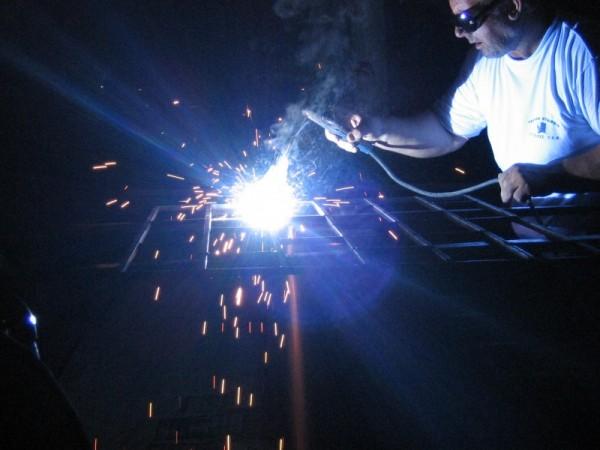 man welding sparkles