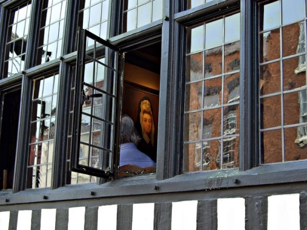 photo of lady looking through a window