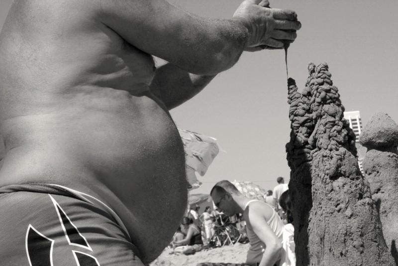 A man builds a sand castle at Santa Monica beach