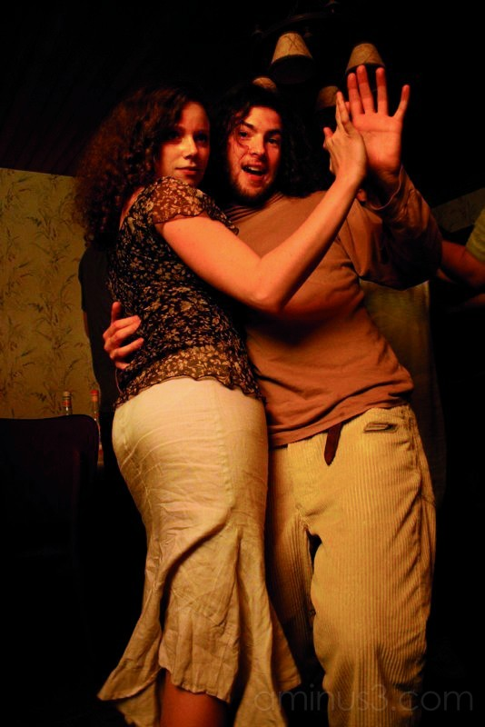 A couple dances in a sepia light.