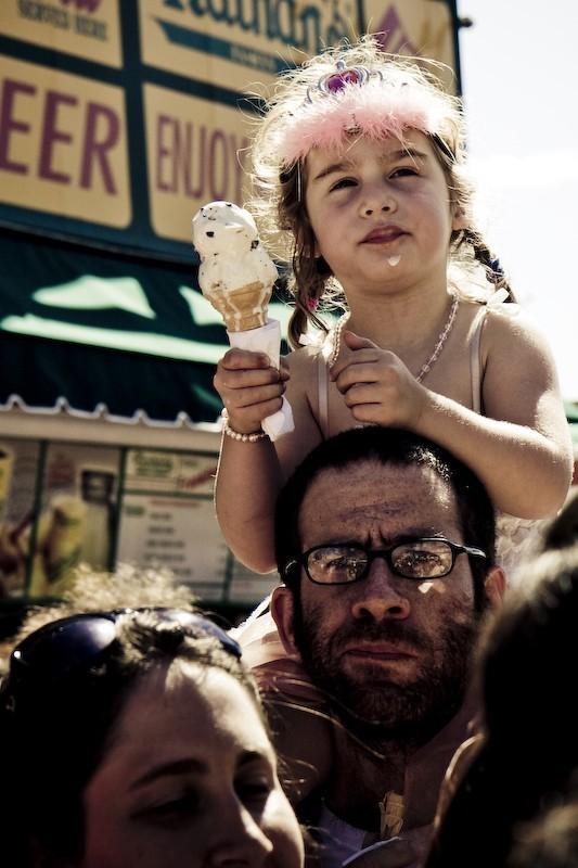 little girl on her dad's shoulders eating icecream