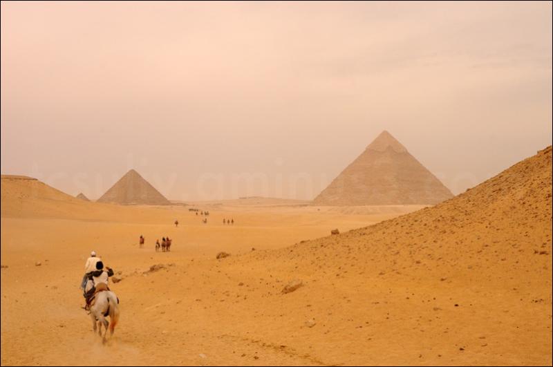 Horsebackers galloping, against pyramid backdro