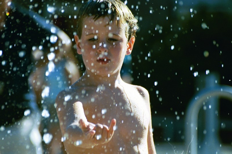 A boy playing in an outdoor fountain