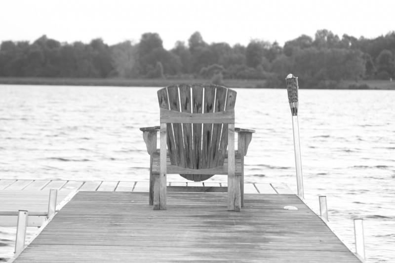 adirondack chair on a lake dock