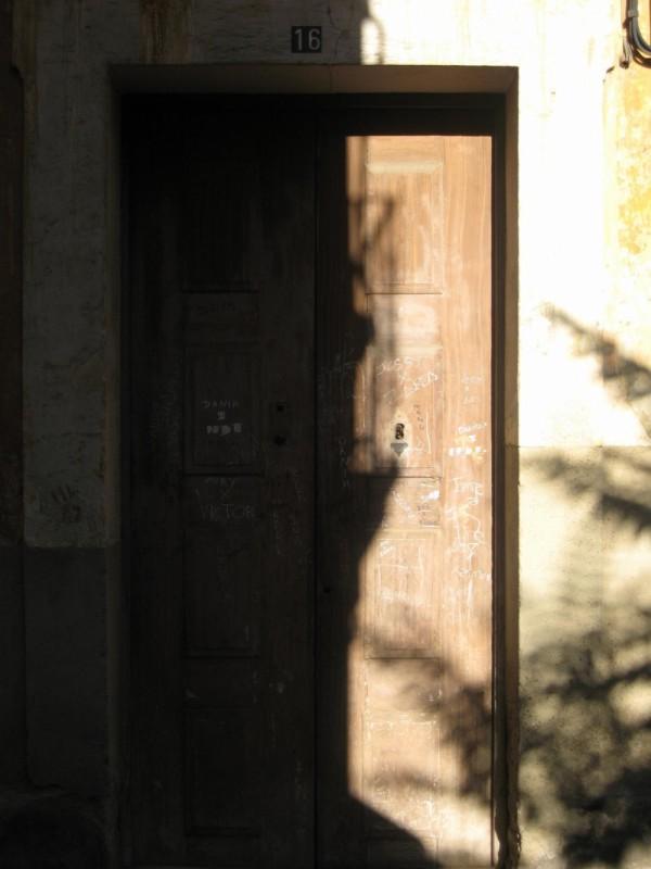Balcón sobre  puerta olvidada y sol a raudales