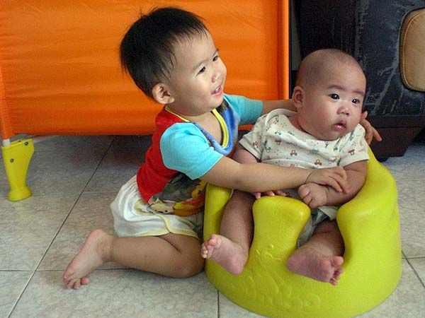 Brother shares bumbo with sister