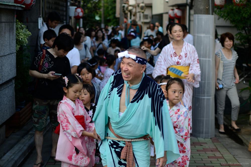 Kimono'd gent leads the procession of the mikoshi.
