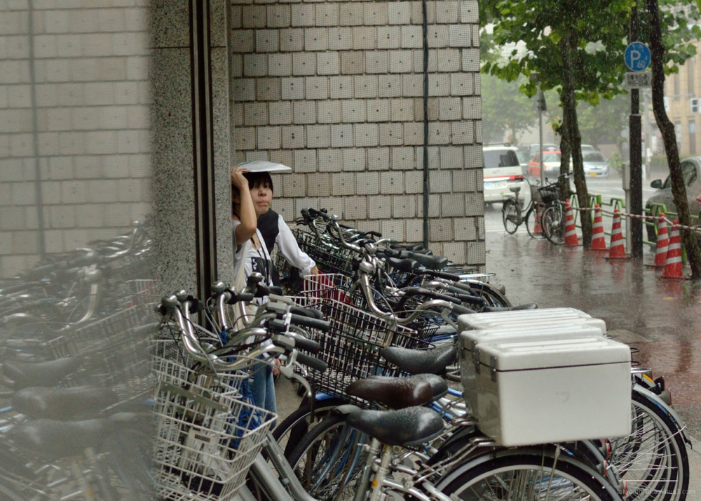 Girl finds shelter from a midday rainstorm.