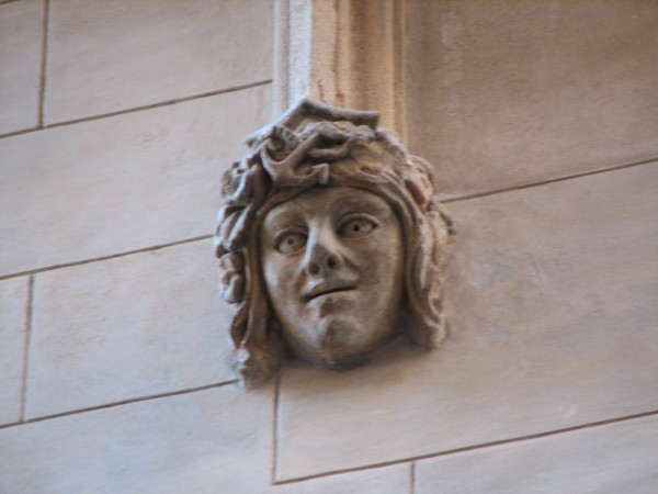 A statue of a face on a building facad