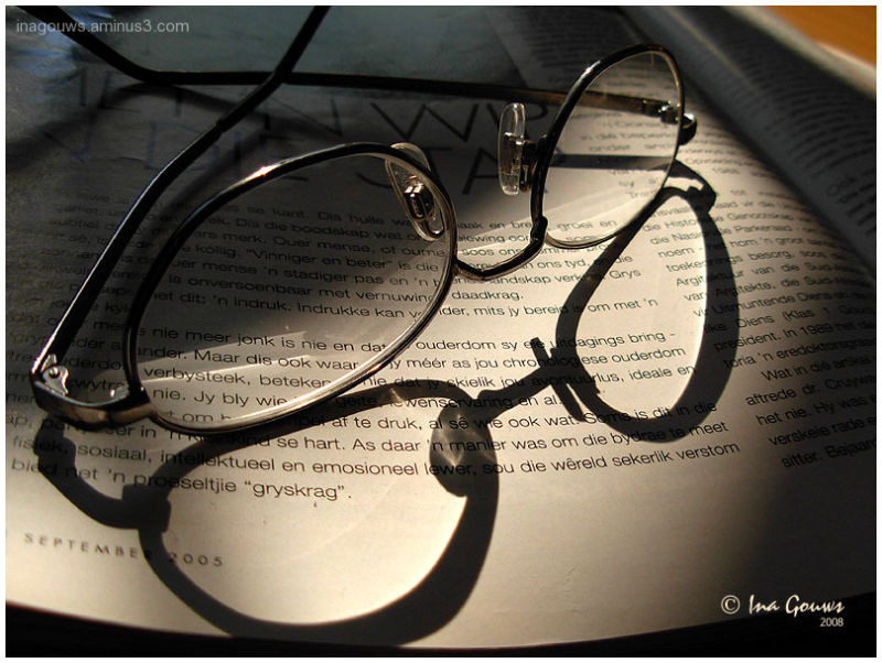 Reading glasses casting a shadow on a book