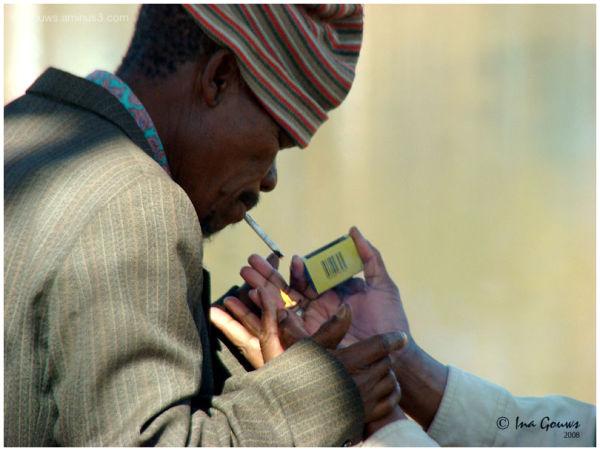 Old man lighting a sigarette