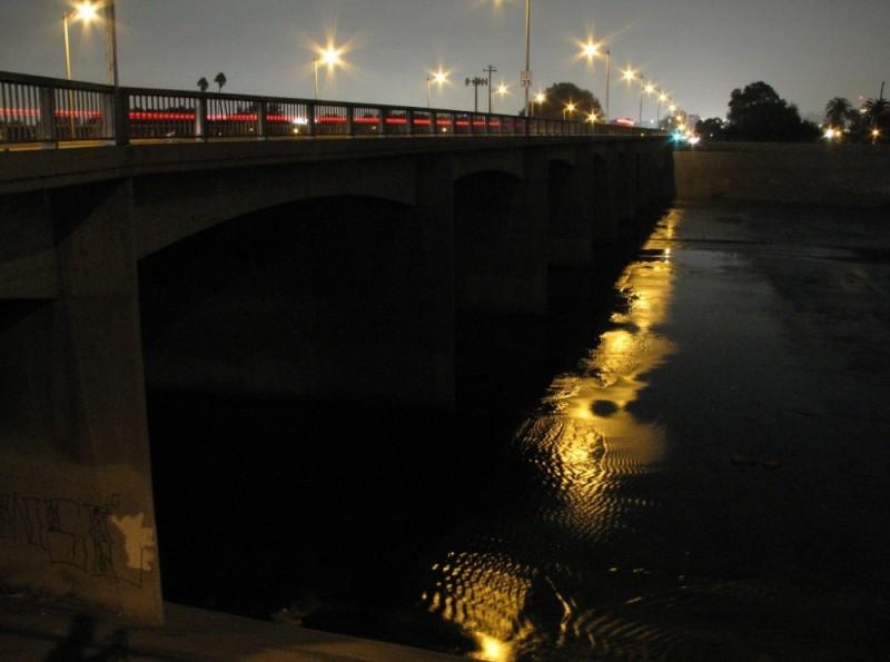 Urban river flowing under bridge at night