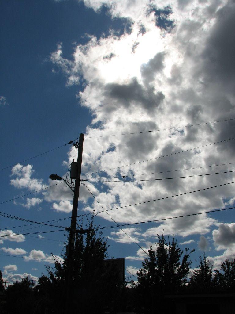 power pole silhouettes against cloudy sky