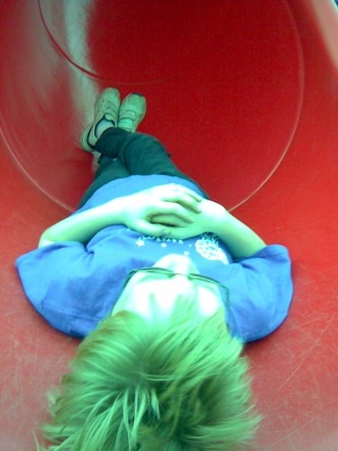 Liam Gallagher relaxes on playground slide.