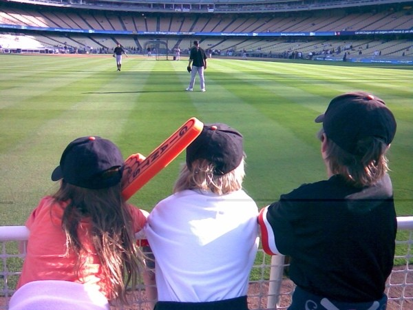 Three young Giants fans watch batting practice.