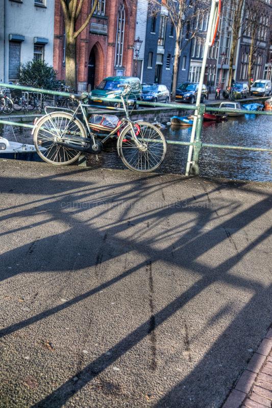 A bike reflection on a canal bridge.