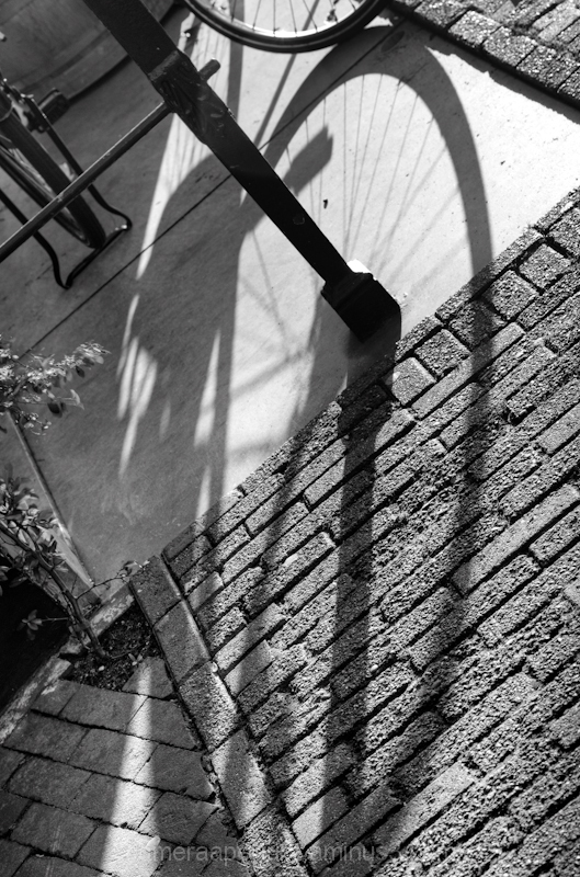 a shadow of a wheel on the ground in Amsterdam