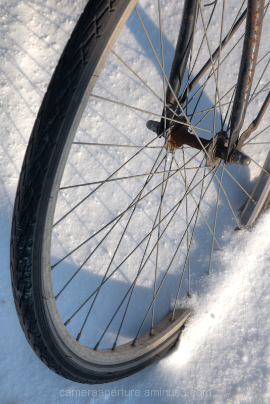 A bike wheel in the snow in the city of Amsterdam