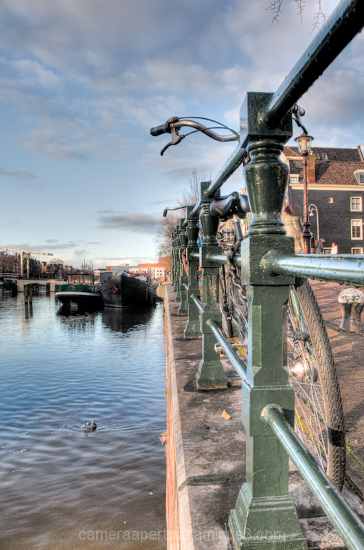 A bike against a railing in the city of Amsterdam