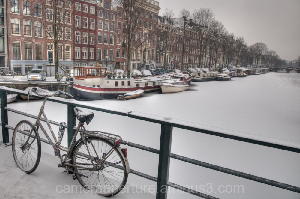 A frozen canal in the city of Amsterdam