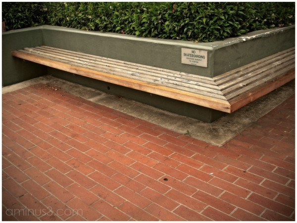 bench sign skateboarding bush wall bricks