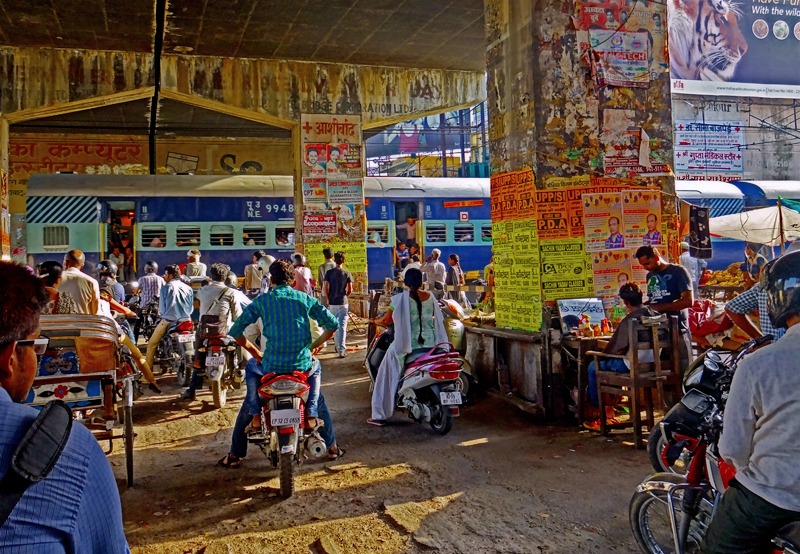 Greetings from India  In this photo, people waiting for a train to pass on their evening commutes in lucknow, india. the man seated in the wooden chair on the right is getting a haircut.