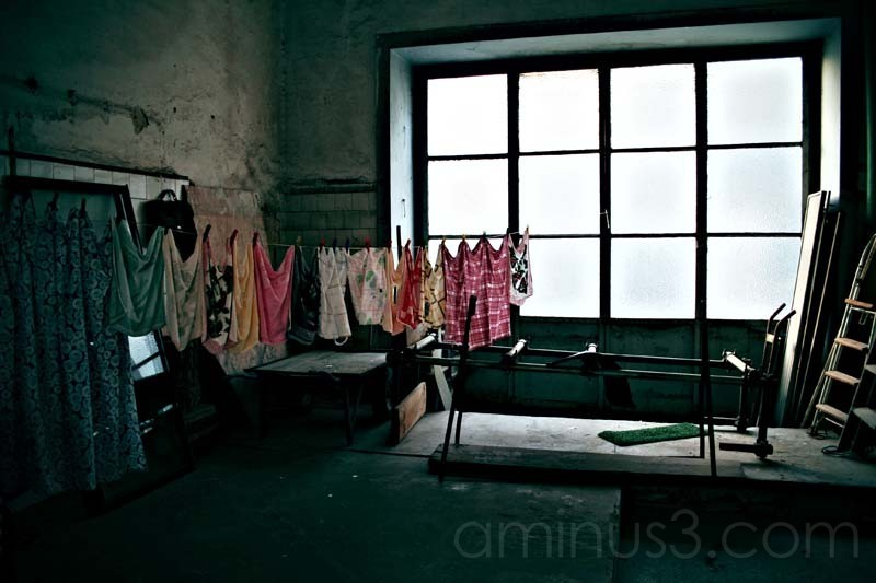 clothes hanging to dry in a dark room