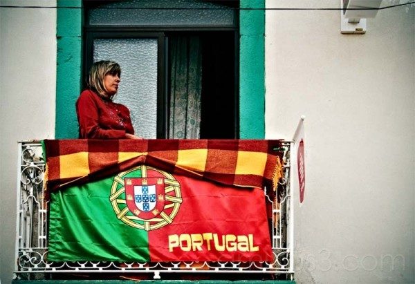 woman at a balcony with portuguese flag