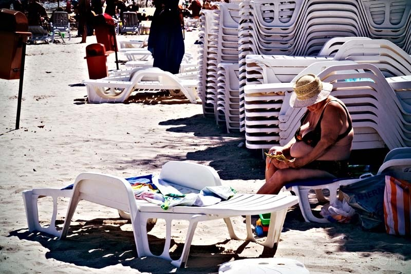 woman sitting at the beach and lots of chairs
