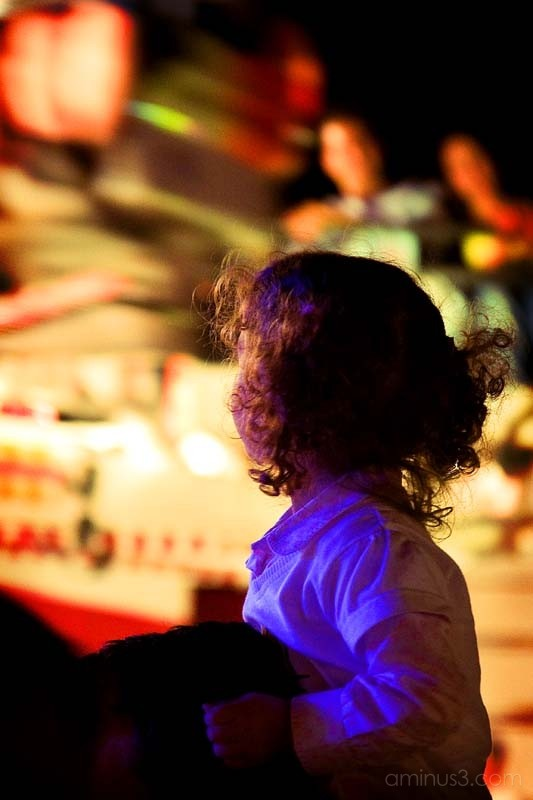 child looking at the lights of a carnival fair