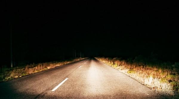 road at night illuminated by car headlights