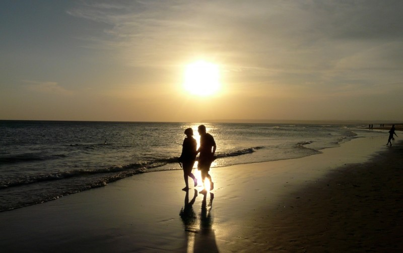 Two people walking by the beach as the sun sets