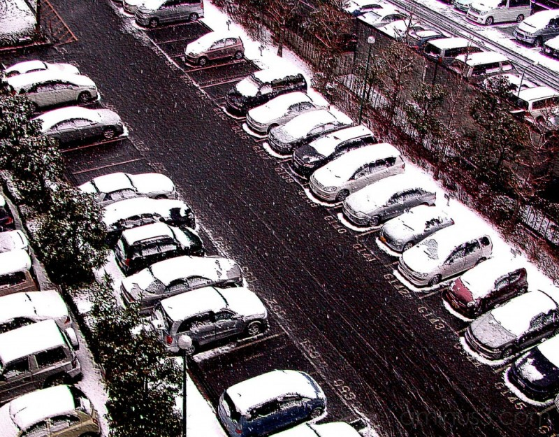 Snow-capped cars in parking lot,suburban Japan