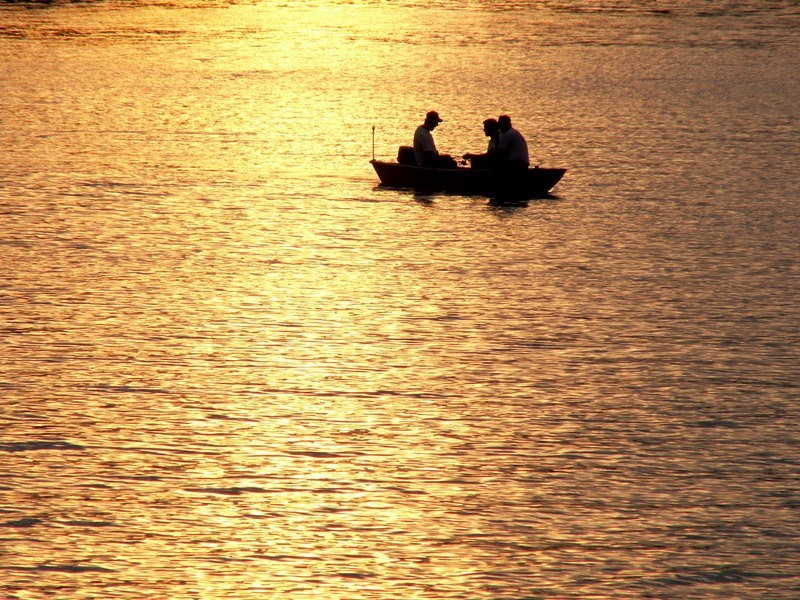 men fishing in a boat at sunset