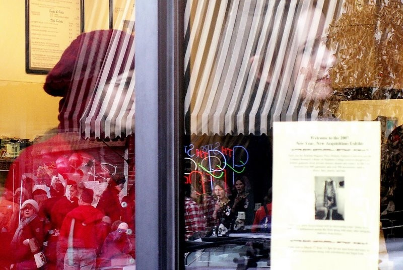 Relections of people in a window.