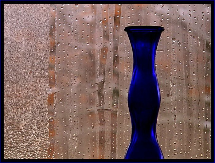 A blue vase in a window filled with condensation.
