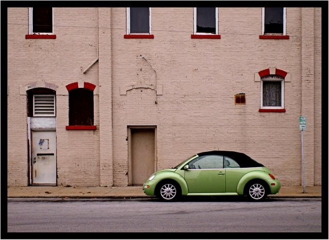 VW car parked in front of a building.