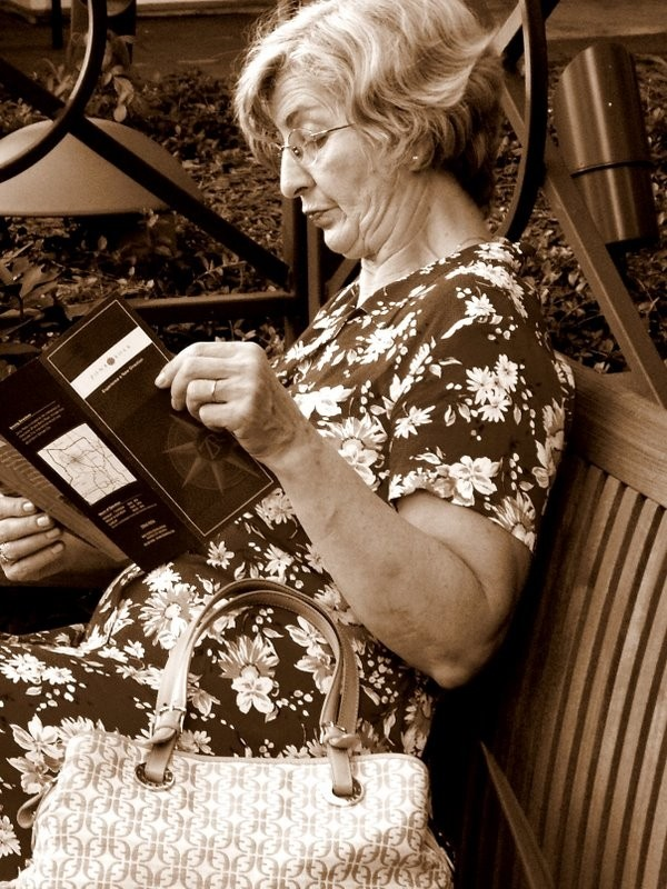 A lady reading a brochure.
