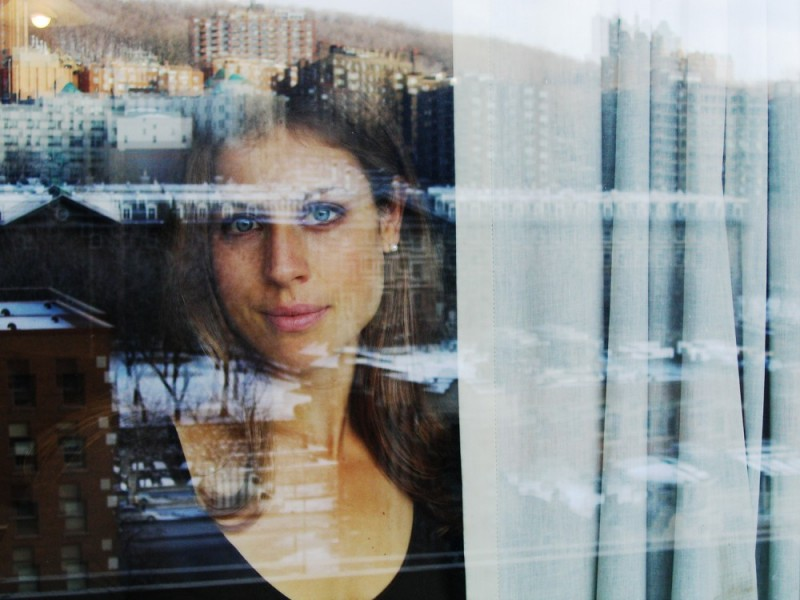 face and cityscape reflected in window