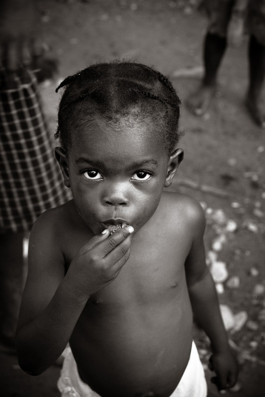 Haitian girl eating a granola bar.
