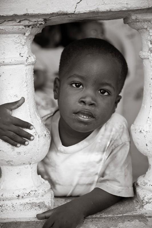 Haitian boy looking through concrete porch