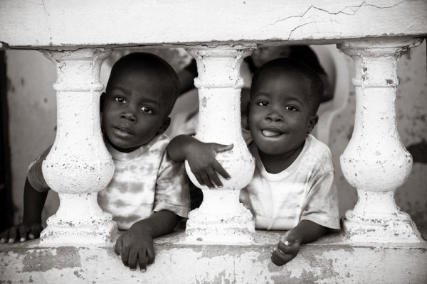 Haitian boys looking through concrete porch