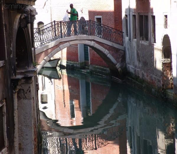 Boy walking across bridge with reflection