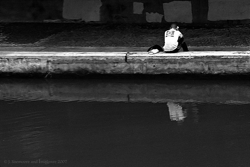 man sitting at the canal