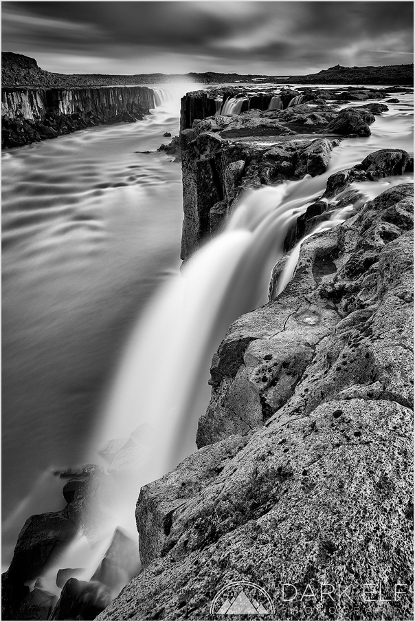"""----------------------------------------------------------------------------------------  Selfoss is a waterfall on the river Jökulsá á Fjöllum in the north of Iceland. This is a composition that I chose from the west side of the river. I focused on one of the """"side falls"""" further away from the main waterfall. The water level was very high and the resulting spray and run off streams prevented me from getting too close.  It was my intention to capture some of Iceland's superb waterfalls with the use of my 6 stop and 10 stop neutral density filters to create moody and dramatic scenes. Selfoss presented me with perfect conditions for what I had in mind. There are plenty of options for different compositions from both sides of the river. Spray is an issue though and wind direction needs to be considered when planning photos in this area."""