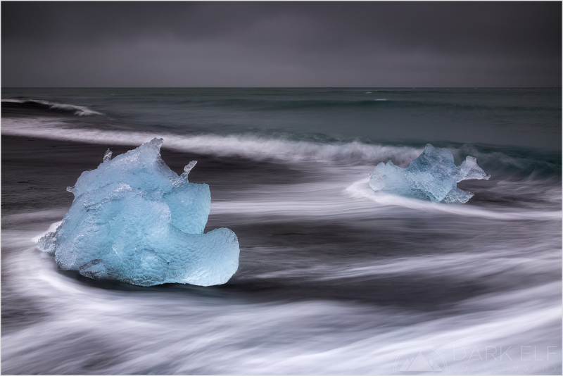 """----------------------------------------------------------------------------------------  Breiðamerkursandur is the Icelandic name for the ice beach near Jokulsarlon Glacier Lagoon in the south of Iceland. It was one of the highlights from out trip to Iceland and I could spend there day after day after day.  I captured a couple of icy """"travellers"""" arriving on the black beach after being pushed out from the lagoon by the receding waters during the low tide earlier in the day. It was a dark and gloomy day but the icebergs were really shining as they landed on the dark sand.  This is my last post for 2015 and I wish everyone the best of light and lots of happiness for 2016. See you all next year!"""