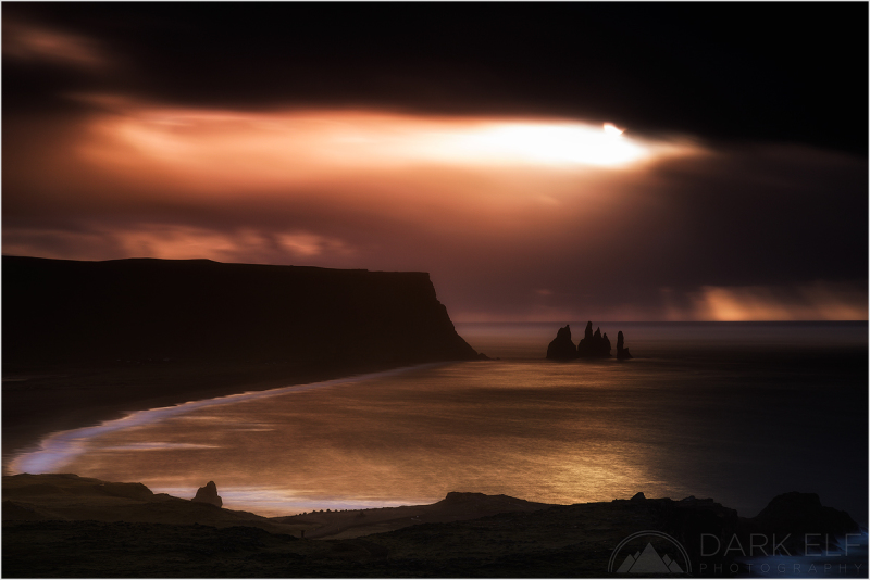----------------------------------------------------------------------------------------  The sun desperately tries to break through dark clouds as it rises over the Reynisfjara Beach and the famous basalt sea stacks - Reynisdrangar, in Iceland.  I spent a great morning shooting from the rocks that you can see in the bottom right hand corner of the scene. I was capturing the Black Sand Beach and the sea stacks from different perspectives before deciding to drive further up the coastal cliff to capture the Dyrhólaey arch.  Sometimes it pays to look around behind you, or in this case in the rear view mirror of my car, to see an amazing sight opening up just when you least expect it. As I was driving up the steep hill towards the arch, I looked in my mirrors to see a break in the clouds opening up and this dramatic and contrasting scene developing very quickly. The wind was picking up sharply and the clouds were moving rapidly across the sky. I stopped on the side of the road immediately and had just enough time to shoot three or four frames.  It was one of those moments when I was really pumped up to see the results on my camera screen. I did not make it to the arch in the end but I was more than happy with the shots I took on the way.